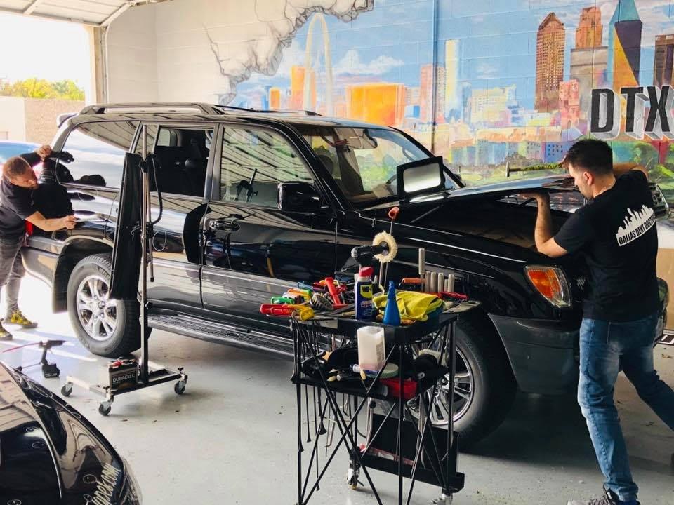 2 guys working on black suv car