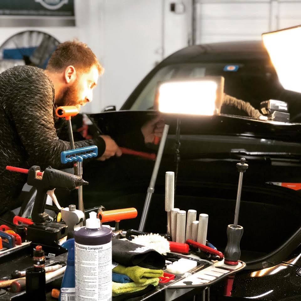 guy fixing car dent