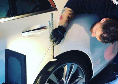 guy fixing car fender dent